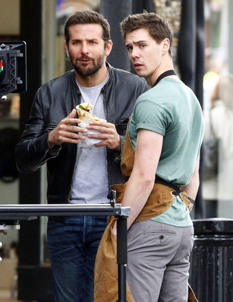 "Bradley Cooper munched on a gyro while filming ""Adam Jones"" with Sam Keeley in London."