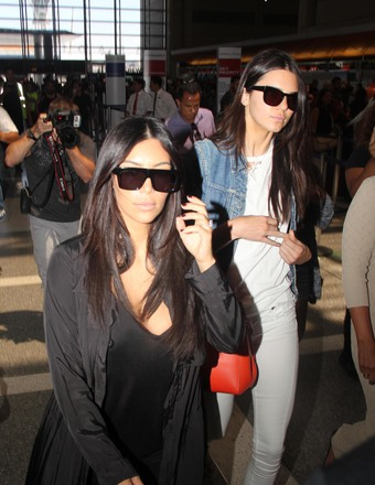 Kim Kardashian and Kendall Jenner were mobbed by paparazzi at LAX.